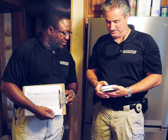 Two fire department officers install a fire detector.